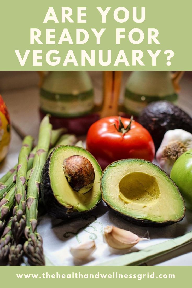 Pinterest sized image showing halved avocado tomato asparagus, garlic and onion to promote veganuary