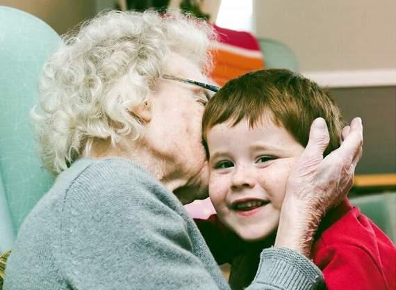 young boy giving elderly lady a hug in nursing home
